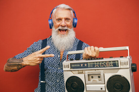 Happy senior man listening to music with wireless headphones and vintage boombox outdoor