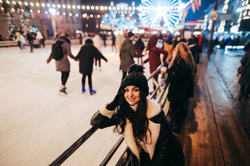 Happy girl in warm clothes stands in the evening near the rink on the background of the Christmas street and people, looks at the camera and smiles. Entertainment on Christmas weekend. Fotomurales