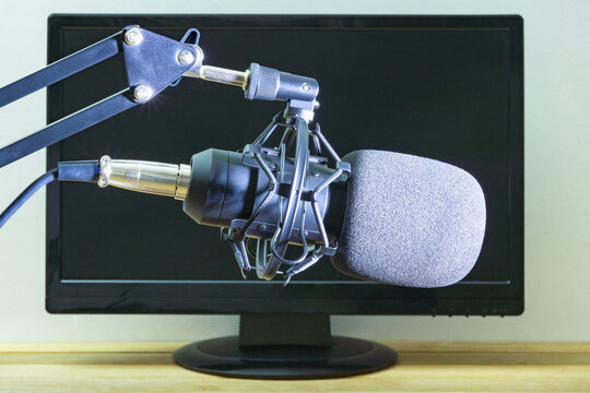Condenser, studio microphone on the background of a computer monitor
