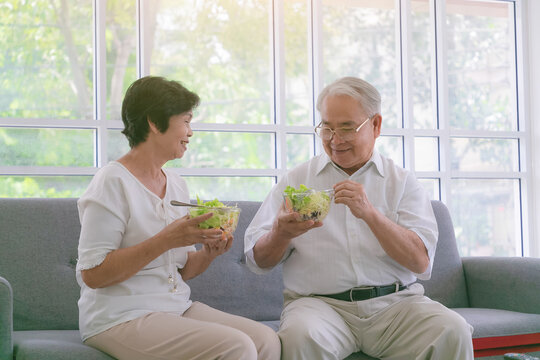 Couple senior eating salad in living room. Delicious and healthy breakfast on the summer day.