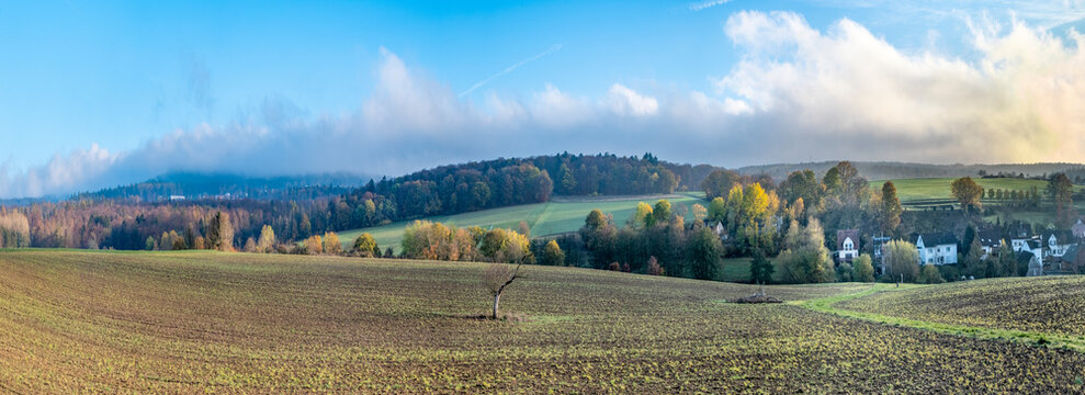 scenic taunus landscape with village, fields and blue sky with clouds