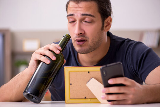 Young male alcoholic suffering from unhappy love at home