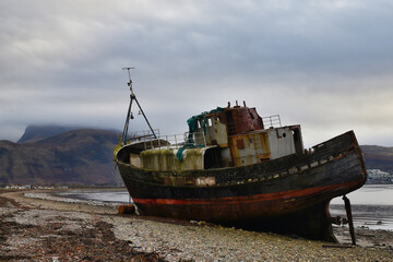 Old ship wreck rusting on the beach at Corpach near Fort William, Scottish Highlands, with Ben Nevis in background