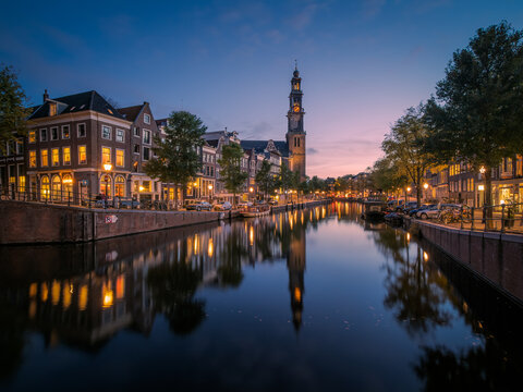 View over the Prinsengracht canal to the Anne Frank House and the Westertoren church tower at dusk