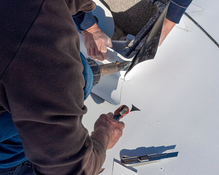 Worker applies pvc membrane roller on roof very carefully. Correct welding with hand-welder, corner.