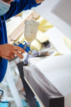 Vertical shot of a furniture maker spraying upholstery adhesive over a prepared foam