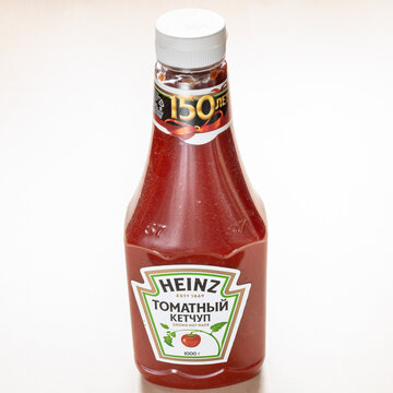 MOSCOW, RUSSIA - NOVEMBER 4, 2020: russian 150th anniversary edition bottle of Heinz Tomato Ketchup on light brown board. Heinz Tomato Ketchup produced by the H J Heinz Company as part of Kraft Heinz