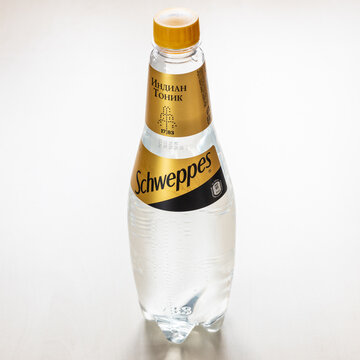 MOSCOW, RUSSIA - NOVEMBER 4, 2020: russian edition plastic bottle of Schweppes Indian tonic water on light brown board. Schweppes is the world's first carbonated soft drink brand
