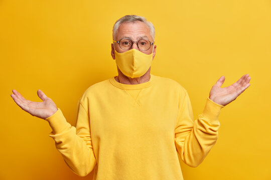 Photo of unaware grey haired man doesnt know how what happening spreads palms and stands confused against yellow vivid wall wears protective mask during coronavirus pandemic. Health care in old age