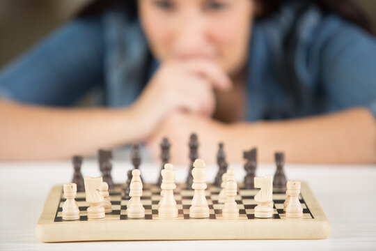a woman is playing chess alone