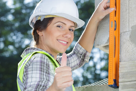 woman showing thumb up with building a wall