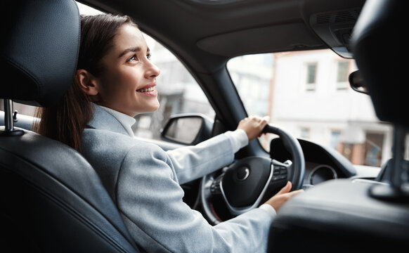Happy elegant woman driver looking at person sitting in her car, pick up passenger. Businesswoman drop friend to meeting. Female executive talking to someone through car window