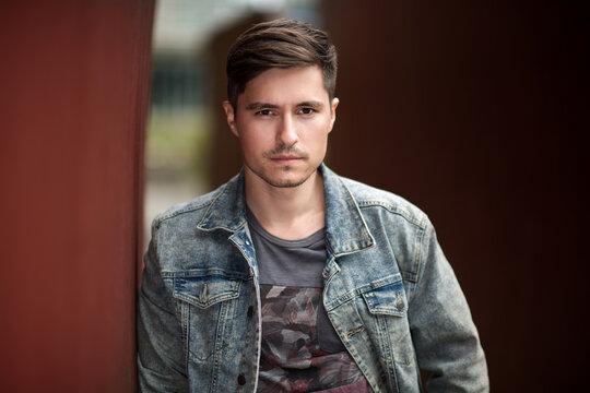 Handsome man posing near a wall wearing jeans jacket