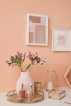 Two pictures in frames on wall by table with flowers in vase and other stuff