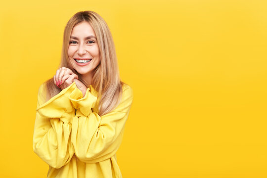 Portrait upbeat pleasant looking glad young blonde woman in yellow smiling and looks into the camera with love, keeps hands together under chin, enjoying life isolated in studio