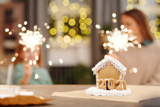 Tasty gingerbread house standing on table against sparkling bengal lights