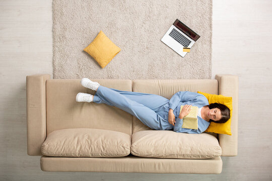 Top view of restful female in blue pajamas napping with open book on chest