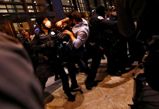 A man is thrown into the air by Washington Metropolitan police officers as Trump supporters and anti-fascist protesters clash at the front door of the Capital Hilton hotel in downtown Washington,