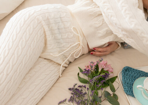 Woman dressed on a comfortable wool loungewear laid on bed.