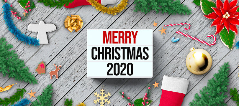 lightbox with message MERRY CHRISTMAS 2020 and christmas decoration on wooden background