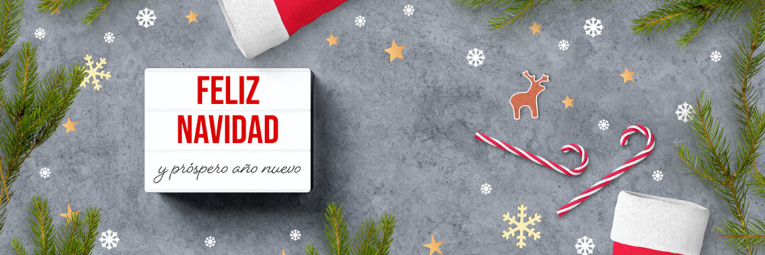 lightbox with Spanish message for MERRY CHRISTMAS AND HAPPY NEW YEAR and christmas decoration on concrete background