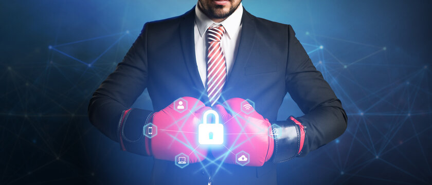 businessman with boxing glove and digital interface showing devices around a lock symbol on abstract background
