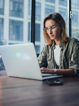 Woman working on laptop. Freelancer at remote work. Female student learning on-line via computer. Blogger or journalist writing new article.