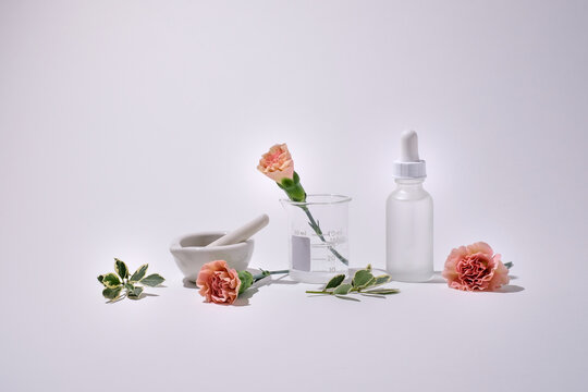 Cosmetic skin care product with pink flower on white background. Natural beauty concept with white mock up bottle .