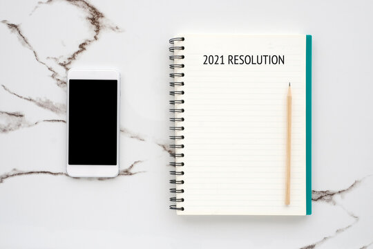 20121 resolution on blank notebook paper, smart phone with blank screen on white marble background, 2021 new year mock up, template, flat lay