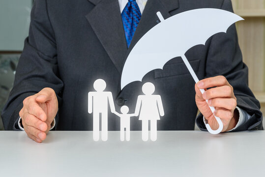 Businessman hold an umbrella and protects or guards family members e.g parents dad, mom and a child