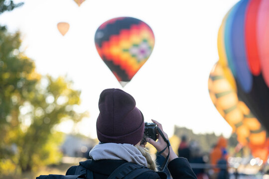 Woman photographer taking pictures of hot air balloons at sunrise