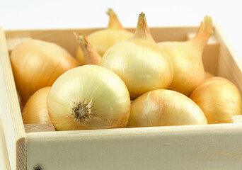 Organic onions in wooden box. Delivery healthy food.