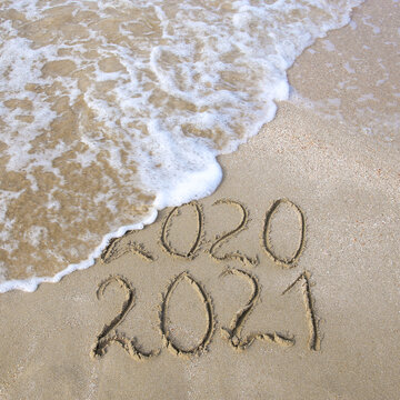 2020, 2021 years written on sandy beach sea. Wave washes away 2020.