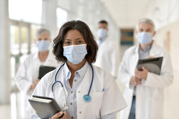 Group of doctors standing in hospital corridor with face mask