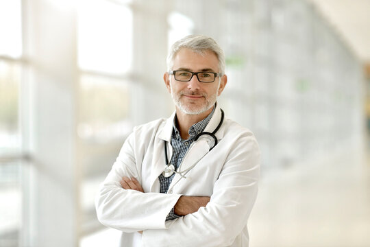 Portrait of confident doctor with grey hair standing in hospital hallway