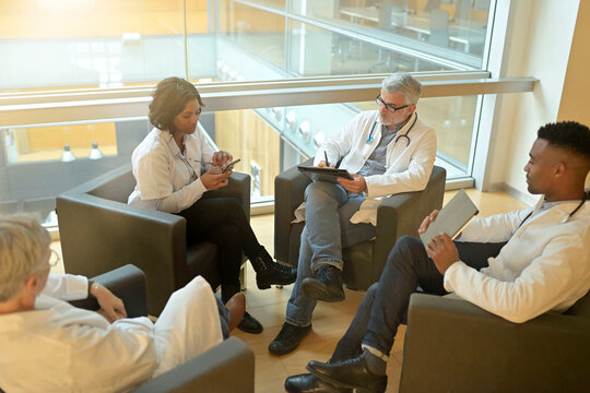 Medical people sitting in meeting room, checking planning together