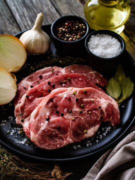 Raw pork chops with onion garlic and seasonings on plate on wooden table