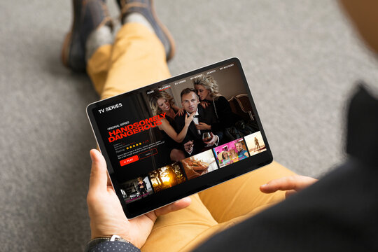 Man looking TV series and movies via streaming service on his digital tablet