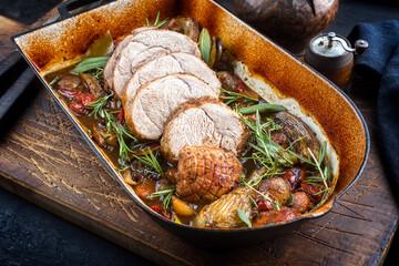 Traditioneller geschmorter deutscher Rollbraten vom Kalb mit Gemüse und Kräuter angeboten als close-up in einer rustikalen Schmorpfanne