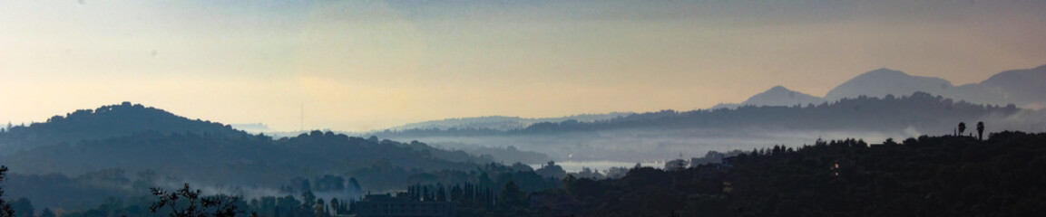 Panoramic landscape view of cypress and olive tree groves on misty rolling hills and valleys of corfu greece