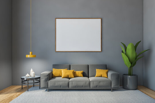 Hall with frame blank canvas and grey sofa against grey wall