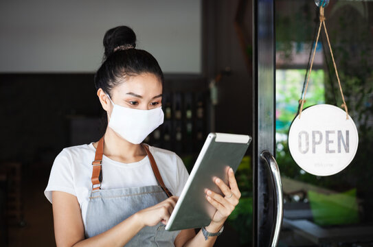 Happy Thai waitress with protective face mask, holding a tablet,  restaurant reopening, Thailand, Koh Phangan