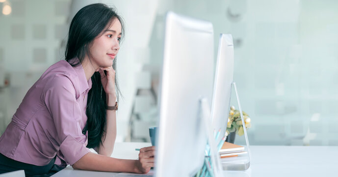 Portrait of young asian woman in casual wear working on personal computer while sitting in modern office, copy space.