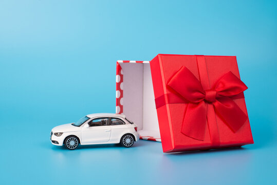 Giving and receiving gifts concept. Close up photo of white toy car beside open red giftbox with bow isolated on blue background