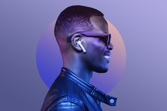 Portrait of smiling african american man listening music with earphones, wearing black leather jacket, isolated on purple background