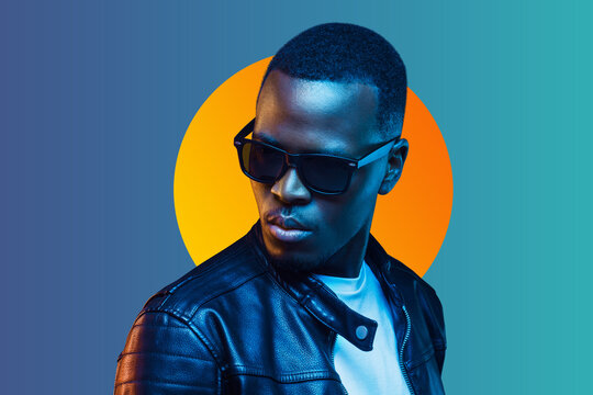 Portrait of stylish black young man wearing leather jacket and sunglasses, isolated on blue gradient background