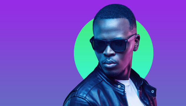 Portrait of stylish african man, wearing leather jacket and sunglasses isolated on purple background