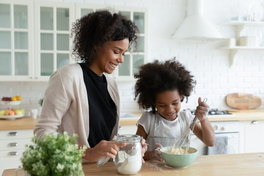 Smiling African American mother with little daughter cooking pancakes, standing at table in kitchen, pretty girl wearing apron using whisk, preparing dough for cookies, family enjoying leisure time