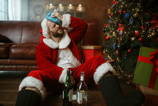 Santa with hangover sitting under christmas tree