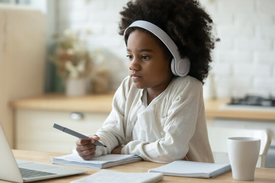 Close up serious African American little girl wearing headphones watching webinar, writing notes, studying online at home, serious child schoolgirl looking at laptop screen, homeschooling concept